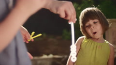 A little girl tries really hard to blow bubbles Stock Footage