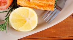 Roast salmon on plate over wood Stock Footage