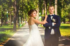Bride and groom standing on park avenue Stock Photos