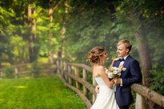 Bride and groom near hedge in wood - stock photo
