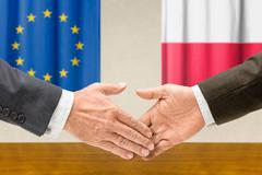 Representatives of the EU and Poland shake hands - stock photo