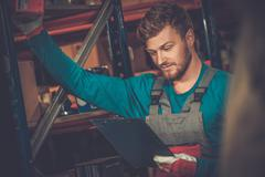 Stock Photo of Worker on a automotive spare parts warehouse