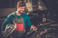Stock Photo of Mechanic with new car headlight in a workshop
