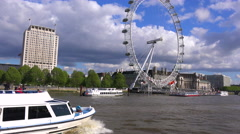 Boats pass the London Eye along the River Thames, England. Stock Footage