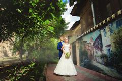 Groom behind bride in park near beautiful building Stock Photos
