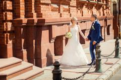 Happy wedding couple near fashionable  building Stock Photos