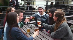Group of friends enjoying a beer at pub in London Stock Footage