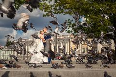 Husband and wife near building with doves flying - stock photo