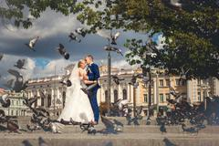 Husband and wife near building with doves - stock photo