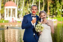 Couple with decorative mustache and lips in park - stock photo