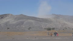 Tourists walking with steaming volcano in background,Bromo,Java,Indonesia Stock Footage