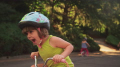 An adorable little girl happily riding her tricycle Stock Footage