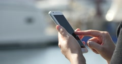4k A girl using a smartphone at seaside,yacht & sailing in the harbour. Stock Footage