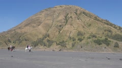 Tourists on horses with Gunung Batok volcano,Bromo,Java,Indonesia Stock Footage