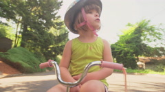 An upset little girl crosses her arms and gets off her bike Stock Footage