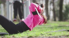 Stock Video Footage of Young woman doing abs exercises at park