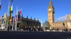 London taxis pass Big Ben and Westminster Abbey, England. - stock footage