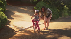 A mother helps her daughter get started on her bicycle and the girl takes off Stock Footage