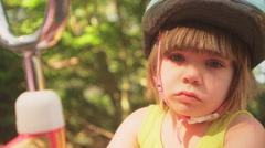 An upset little girl tries picking tape off of her bike Stock Footage