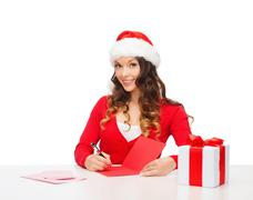 Stock Photo of smiling woman in santa helper hat with postcard
