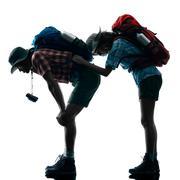 couple trekker trekking tired silhouette - stock photo