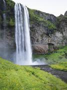 A waterfall cascade over a sheer cliff. Kuvituskuvat