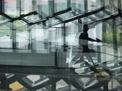 A man walking through the Harpa building, with glass walls and reflected ligh Stock Photos
