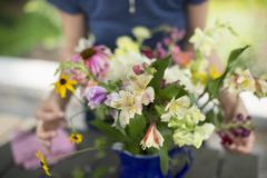 A person arranging a bunch of flowers in a vase. - stock photo