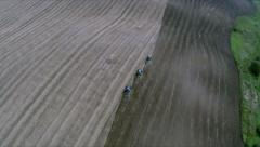 Soil cultivation. Three tractor cultivated soil in a field. Aerial shot Stock Footage