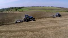 Three tractor cultivated soil. Subsoiler works the soil. Aerial shot Stock Footage