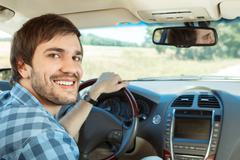 Young man driving his car - stock photo