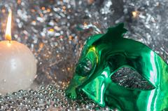 Carnival mask and a candle on a background of shiny tinsel Stock Photos