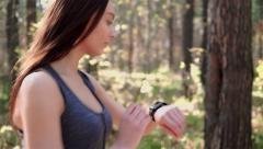 Woman jogging in the morning and looking at smart watches.mp4 Stock Footage
