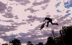 Mountain biker is jumping in front of evening sky - stock photo
