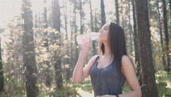 Girl drinks water after jogging in the morning Stock Footage