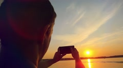 Man taking picture from his mobile phone of beautiful sunset over sea while Stock Footage