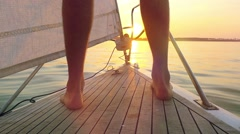 Sunset sailing man on nose of yacht in ocean in slowmotion with flare and Stock Footage