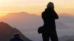 Female photographer making photo of volcano at sunrise,Bromo,Java,Indonesia Stock Footage