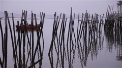 Small boat passing by wooden stakes belonging to the old fishing port Stock Footage