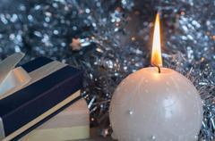 Gift boxes and candle on a background of shiny tinsel Stock Photos