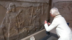 Visitors to the British Museum admire carvings and artifacts excavated at Stock Footage