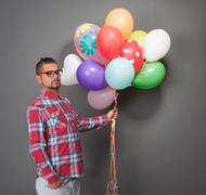 Handsome hipster man with multi-coloured baloons in studio - stock photo