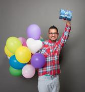 Handsome hipster man with baloons and a present in studio - stock photo