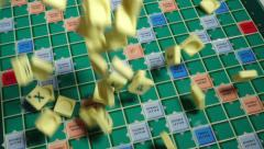 Scrabble Alphabet tiles slow motion falling on Scrabble Board. - stock footage