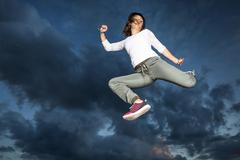 Young woman 19 years old jumping in mid air against the evening sky - stock photo