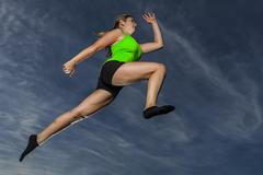 Young woman 18 years old leaping against the evening sky - stock photo