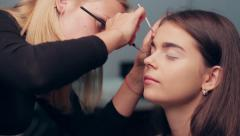 Stock Video Footage of Specialist doing makeup model.