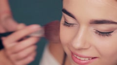 Makeup artist powder face for model. - stock footage