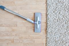 Vacuum cleaner with carpet on parquet floor - stock photo