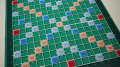 Wide Shot of Scrabble Alphabet tiles slow motion falling on Scrabble Board. - stock footage